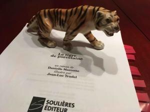 Un tigre en porcelaine déposé sur le jeu d'épreuves.